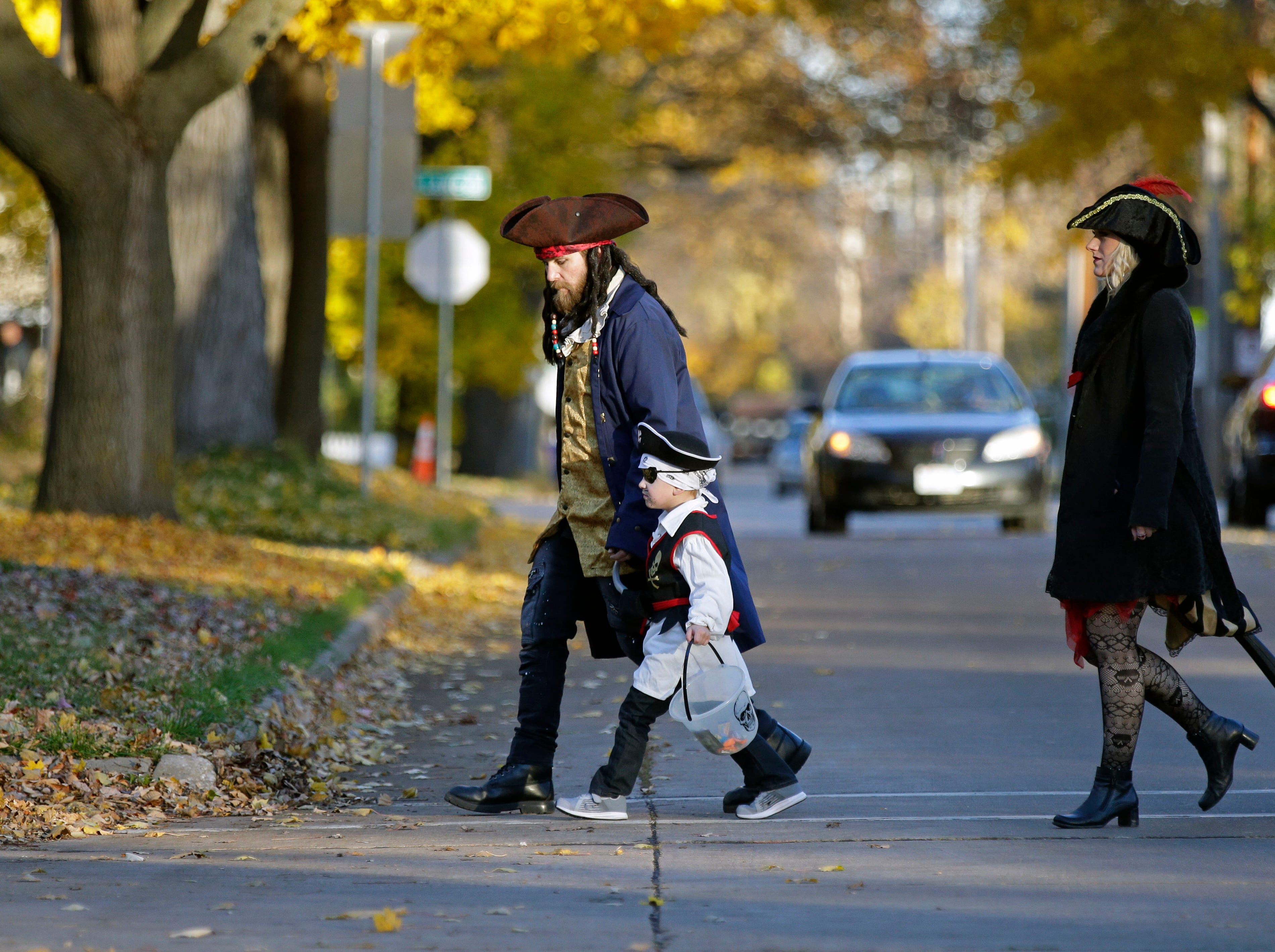 Pirate crew Michael and Chrissie Stevens trick or treat with Jaxson on Halloween Wednesday, October 31, 2018, in Appleton, Wis.