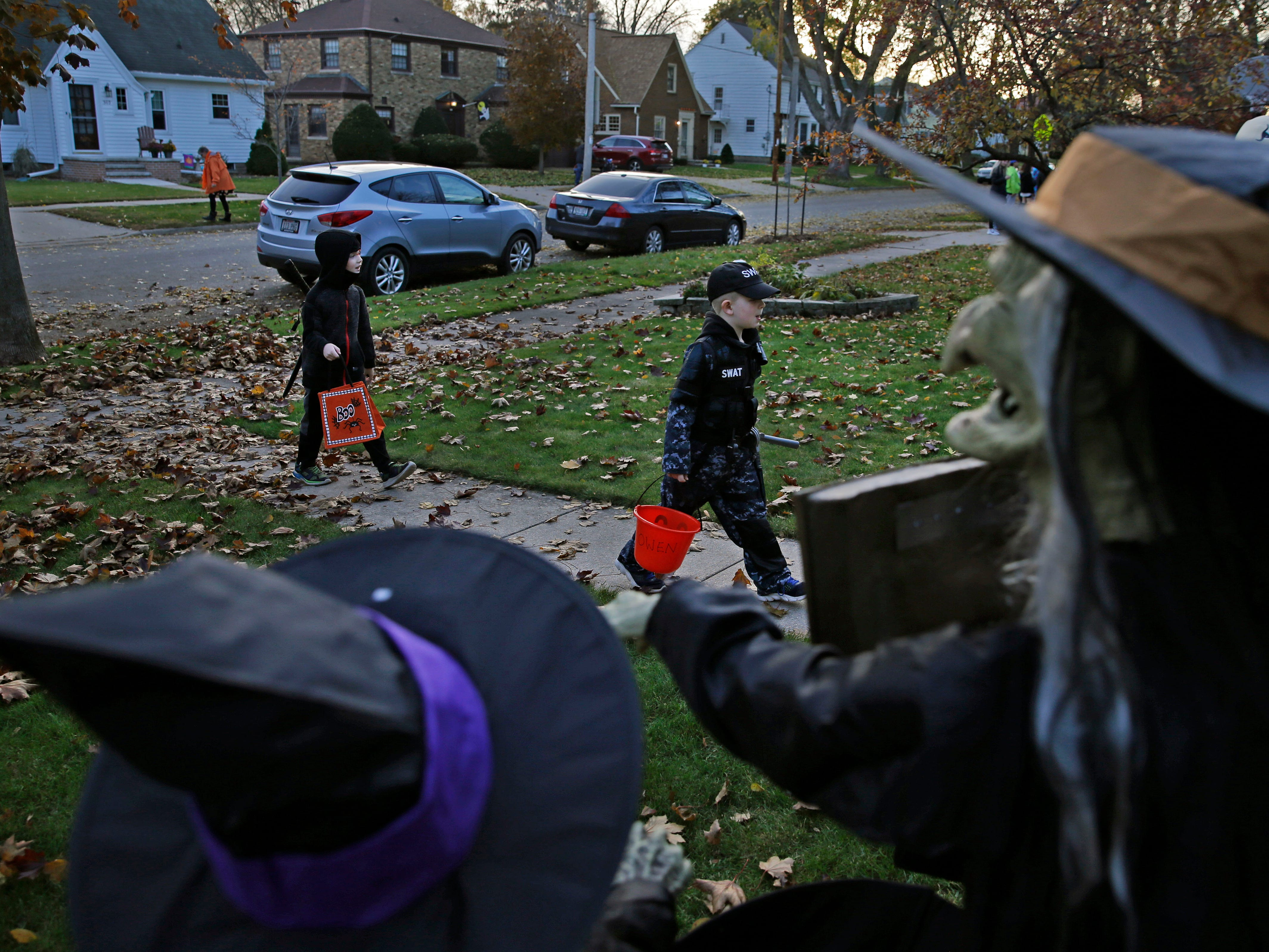 Owen Vandenberg (front) and Logan Walters approach a spooky house as they trick or treat Wednesday, October 31, 2018, in Appleton, Wis.
