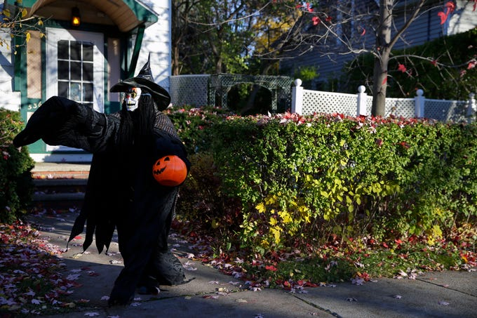 Diane Gerlach waves at passing drivers as she waits for trick-or-treaters on Halloween Wednesday, October 31, 2018, in Appleton, Wis.