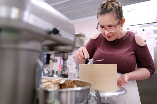 Nea Hahn, owner of Whisk & Arrow Sugar Studio in Appleton, begins the process of decorating a cake.