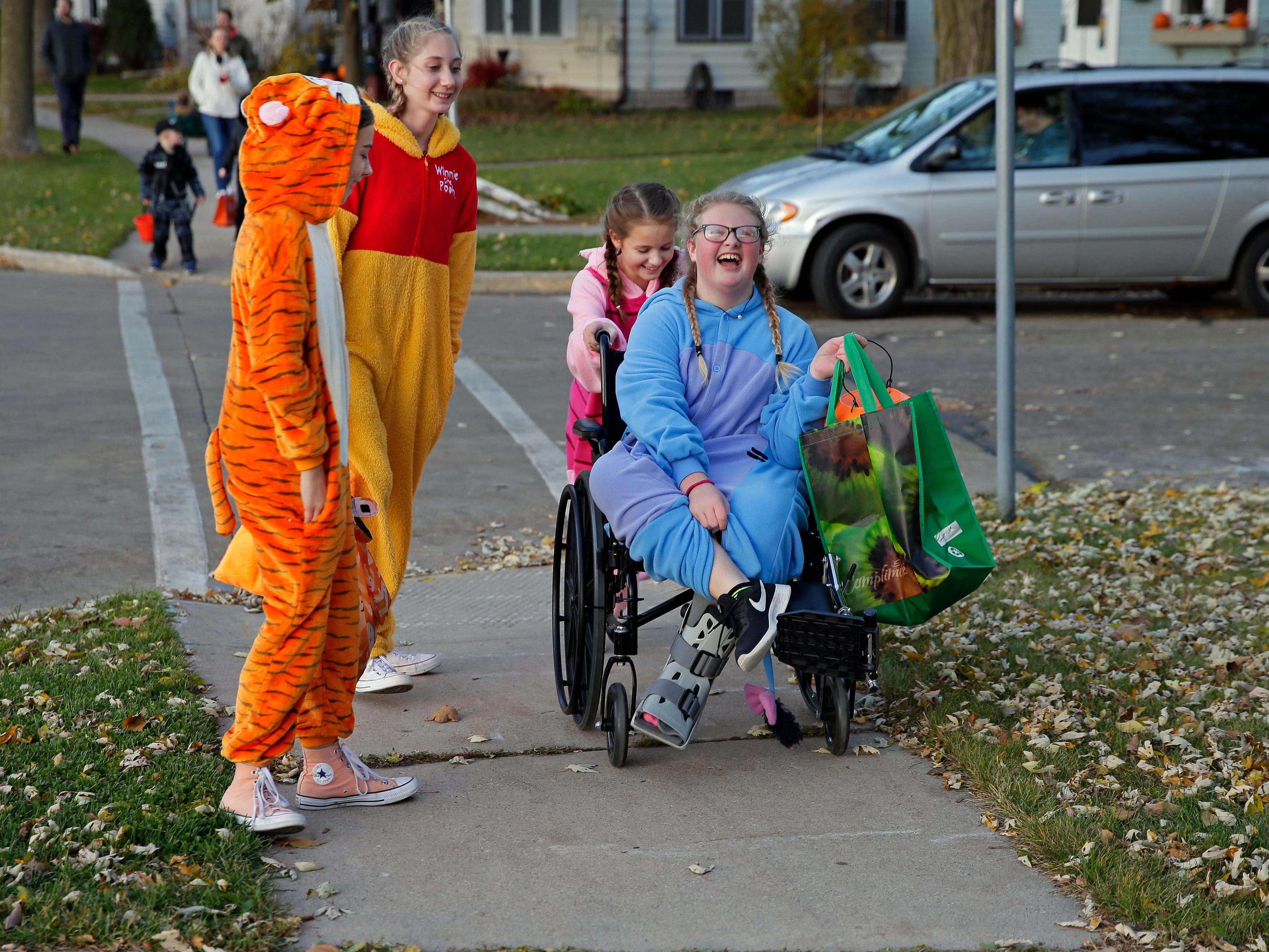 It's Halloween and trick-or-treaters (from left to right) Kate VanderLoop, Megan Conway, Adeline Brzozowski, and Lilli Bird have a laugh as they head to another house Wednesday, October 31, 2018, in Appleton, Wis.
