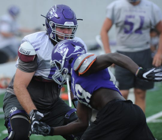 ACU offensive lineman Jon Crisp, left, works a drill during practice Tuesday at Wildcat Stadium.