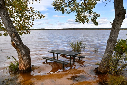 A picnic bench is framed by trees and the water surrounding it on the shore of Lake Abilene Thursday. The lake is 1.2 feet above capacity and still draining from October's record rainfall.