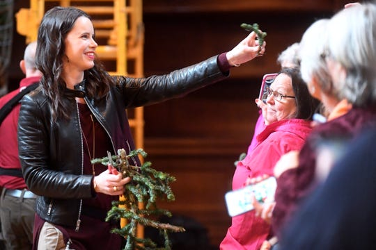 Lizzie Borchers, floral manager at the Biltmore, hands out pieces of a Fraser fir that fell to the ground as it was being raised in the banquet hall Nov. 1, 2018. A team of about 50 employees from various departments raised the tree.