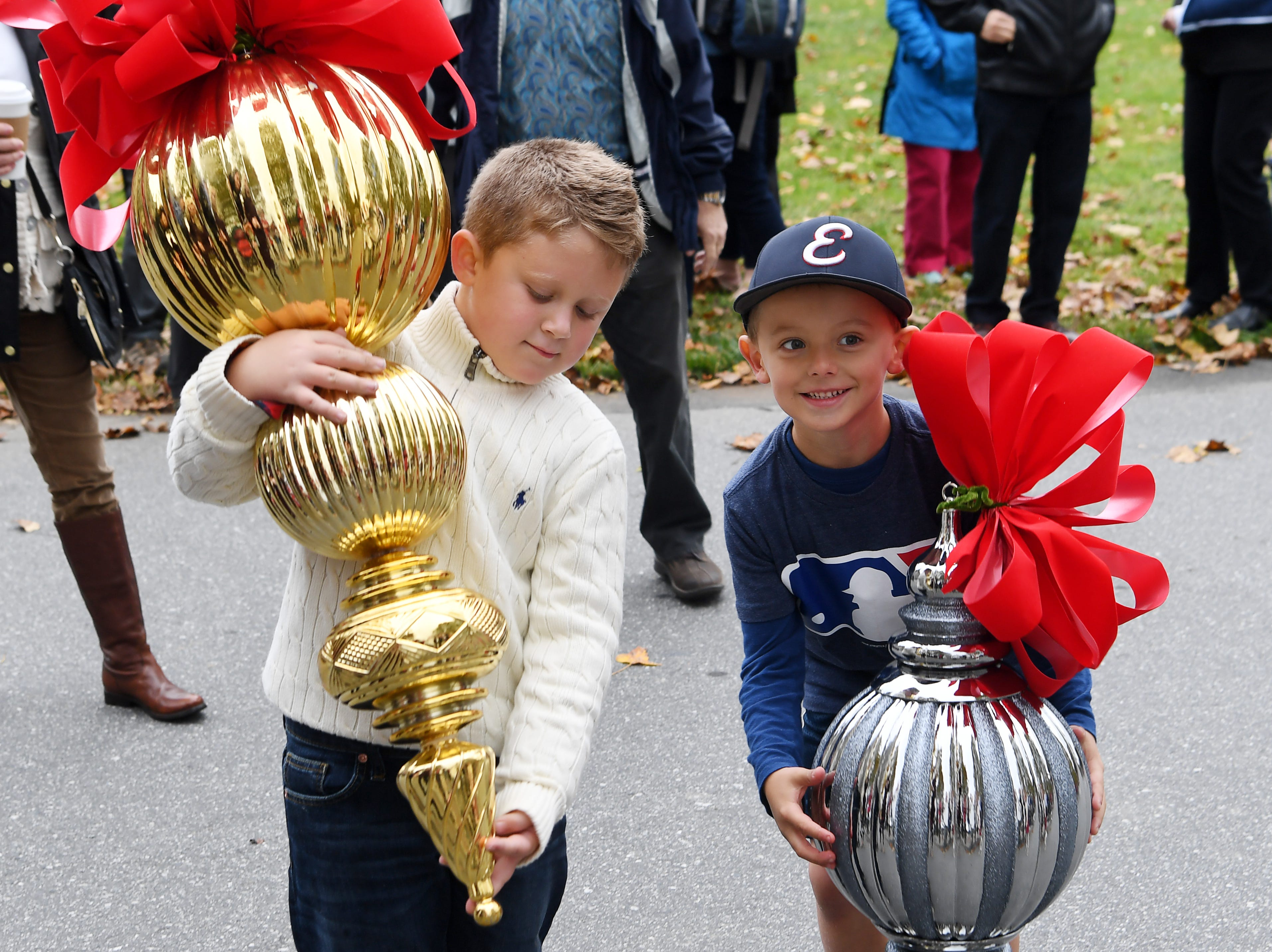 Ethan Johnson, left, and Landry Evans, both 6, pose for a photo holding large ornaments used by the Biltmore as they wait for the arrival of the Christmas tree Nov. 1, 2018.