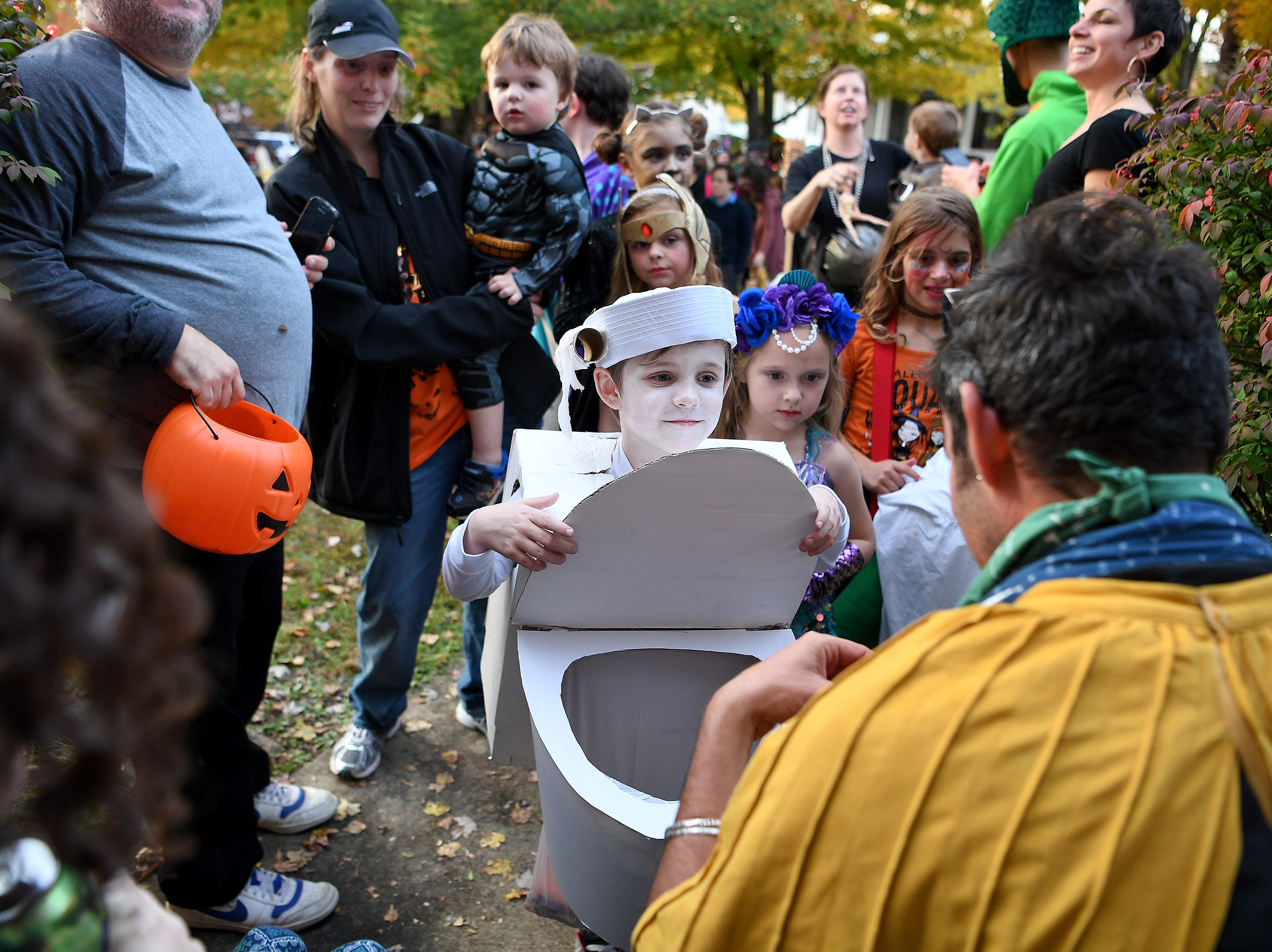 Peyton Carleton, 6, opens up the seat on his toilet costume as he trick-or-treats at a house on Vermont Avenue during their annual Halloween celebration on Oct. 31, 2018.