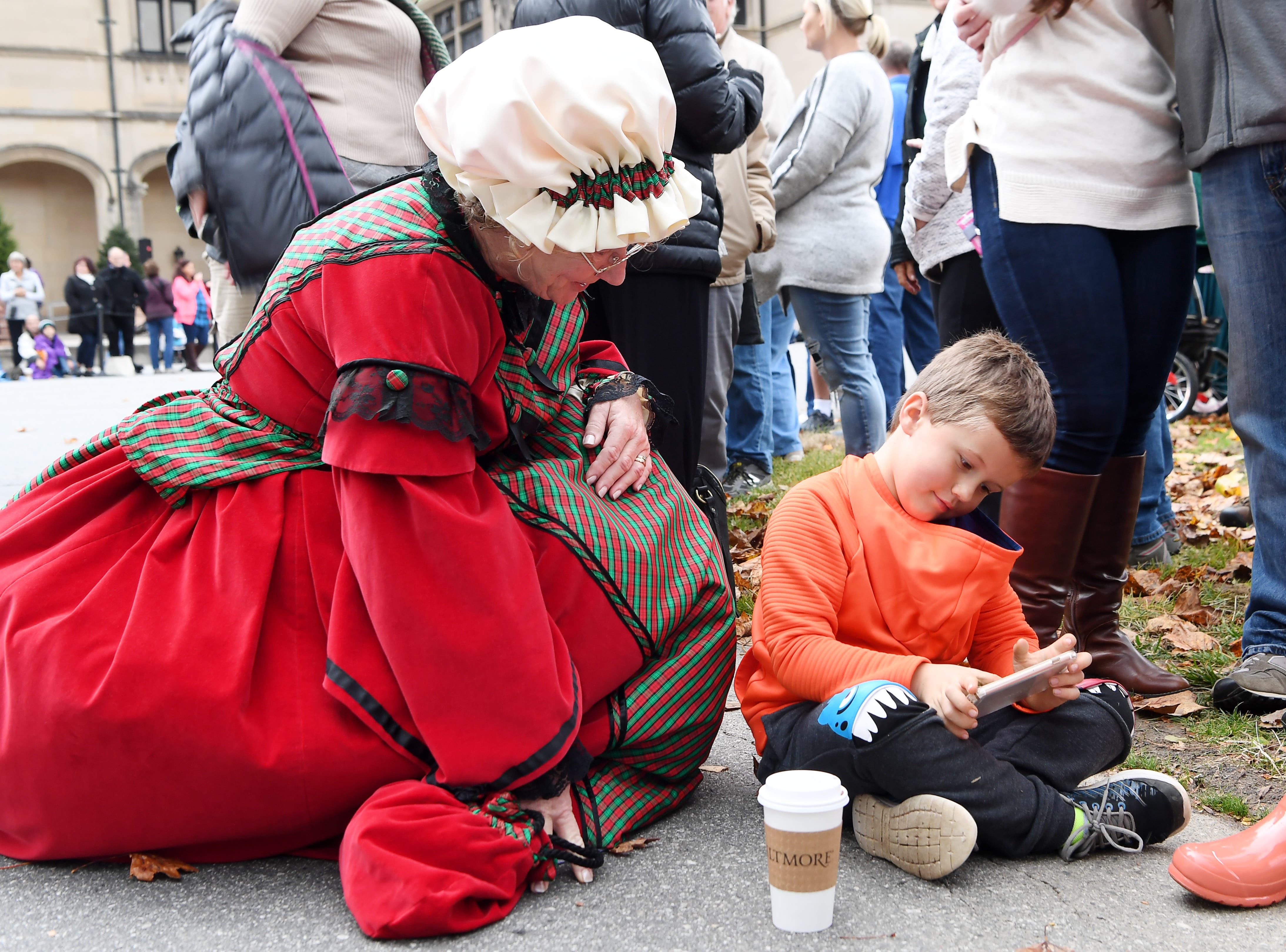 Hunter Henderson, 6, shows Mrs. Claus the game he is playing as he waits for the arrival of the Biltmore's banquet hall Christmas tree Nov. 1, 2018.