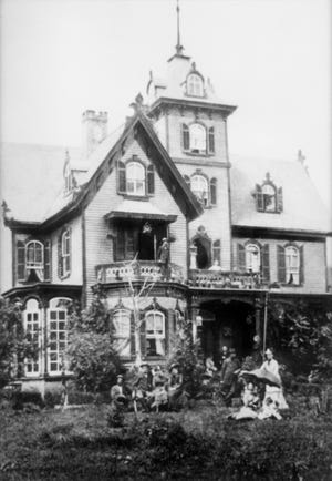 Colonel James Henry Rumough and family gather outside the house, then called Rutland, circa 1890.