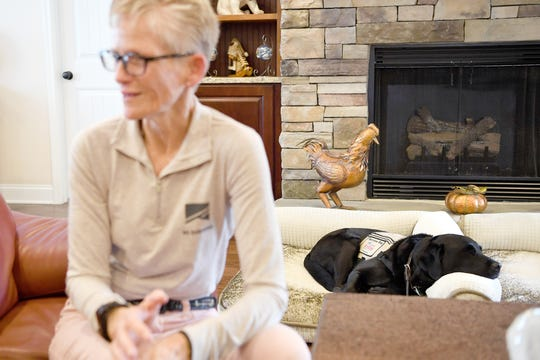 Retired Command Sgt. Maj. Gretchen Evans' service dog, Aura, lays on a dog bed as she talks about her time in the United States Army, a career she loved, and the mortar blast in Afghanistan that deafened her and forced her to retire. Aura does everything for Evans from answering her phone to letting her know when someone is at the front door.