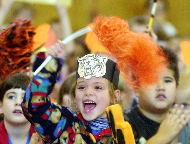 Six-year-old Gina Natale, a first grader, cheers for Union-Endicott High School football team during a pep rally held in 1999 at the Charles F. Johnson School.
