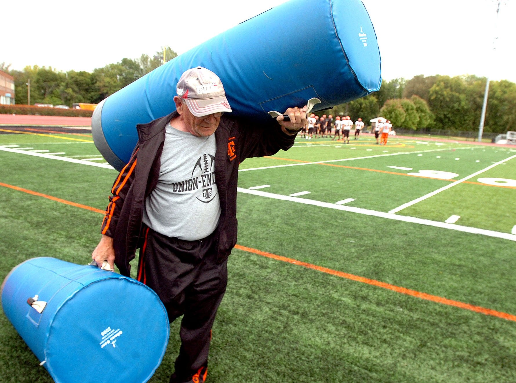 Shorty Bowen carries the cylinder pads off to help keep the football field clear during practice at Union-Endicott. During game nights, Bowen makes sure the visiting sideline is also set, not only the Tigers' side.