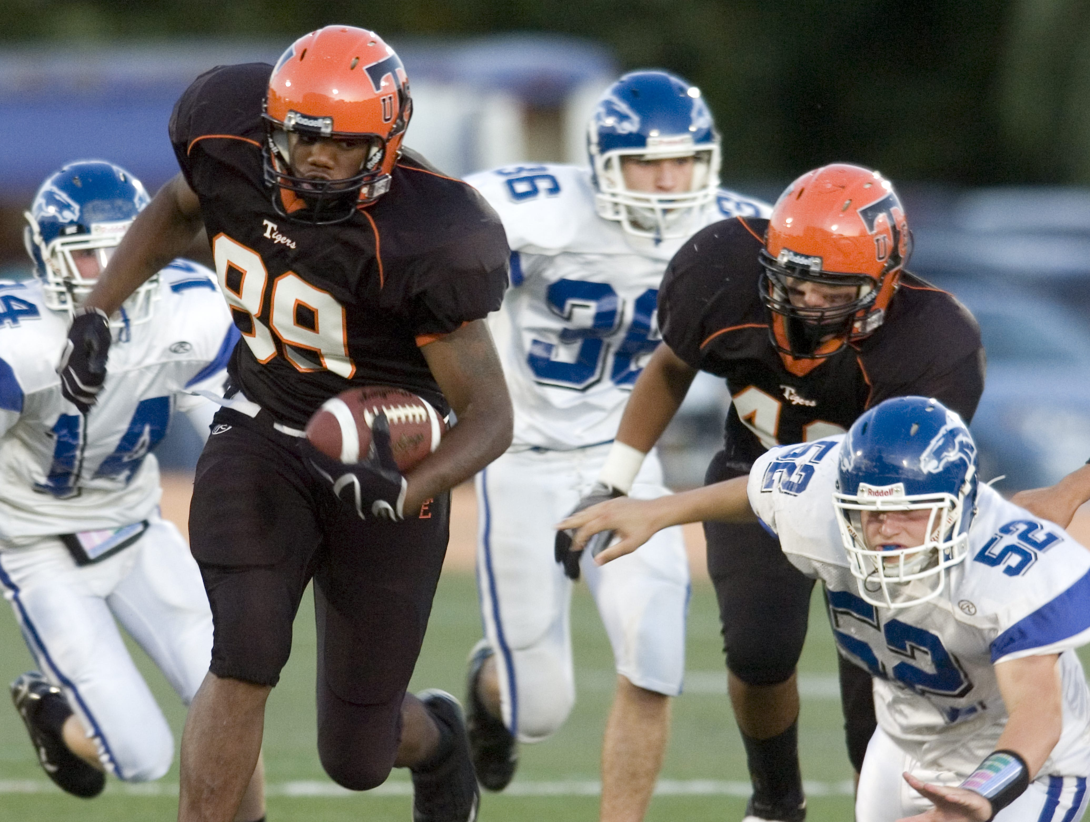 Union-Endicott's Carnell Chandler, left, runs away with the football as Horseheads' Patrick Watson falls on the opening kickoff return of a 2009 game at Ty Cobb Stadium.