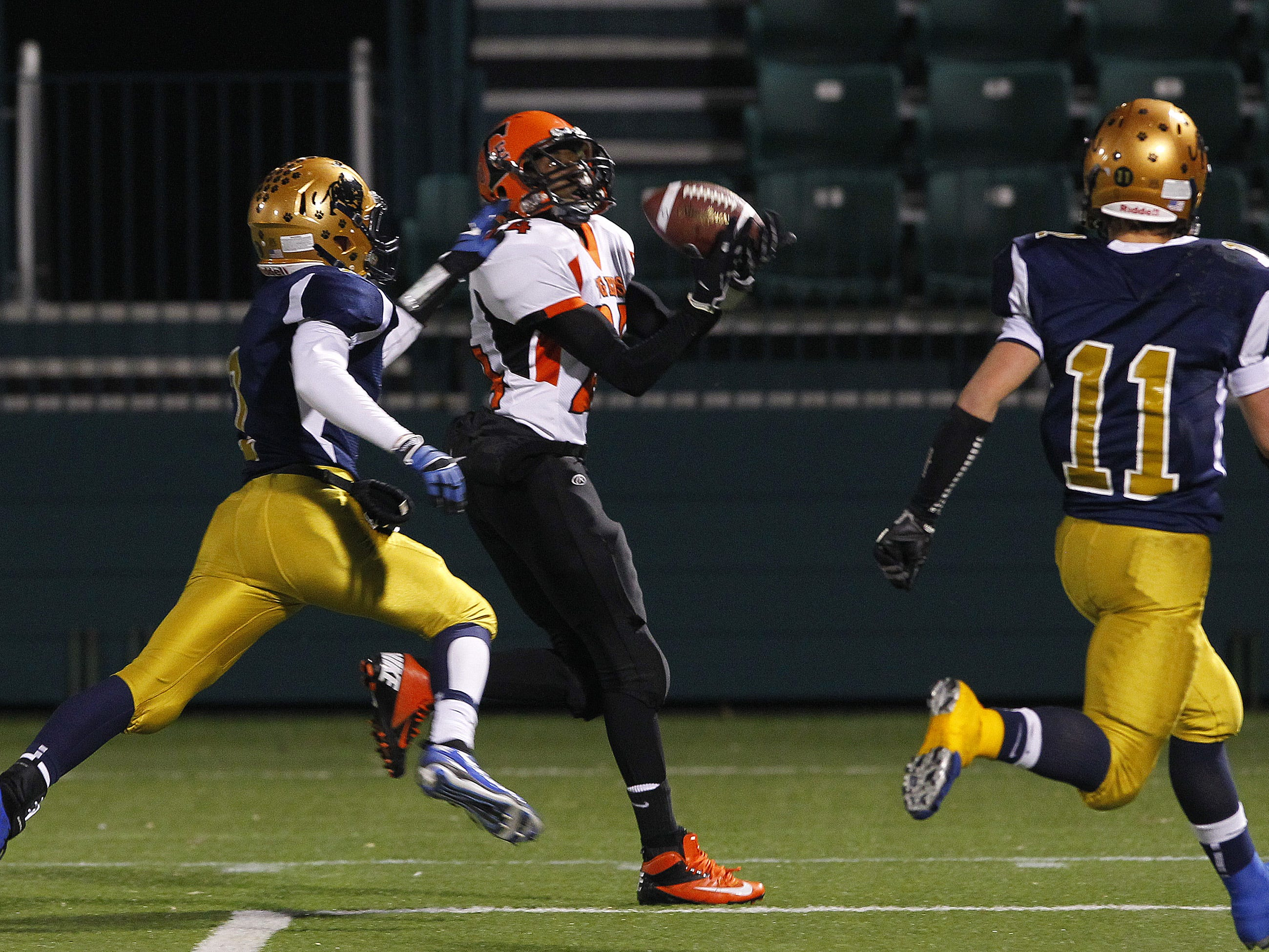 Union-Endicott's Nahjee Miller, center, catches a 31-yard touchdown pass between Sweet Home's Carter Mann, left, and Ethan Reger during NYS Class A semifinal playoff football action football action at Sahlen's Stadium in Rochester Friday evening, November 16, 2012.