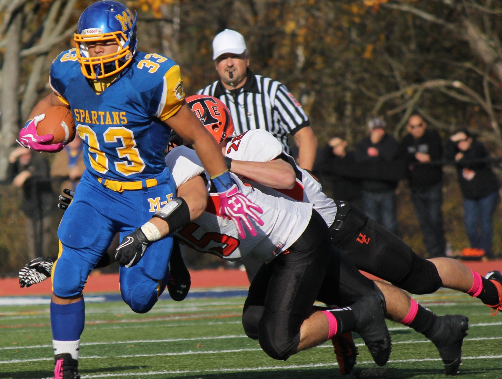 In 2012, Lucas DePofi and Drew Hogan of Union-Endicott try to slow Maine-Endwell's Darnell Woolfolk in the second half at Spartan Stadium.