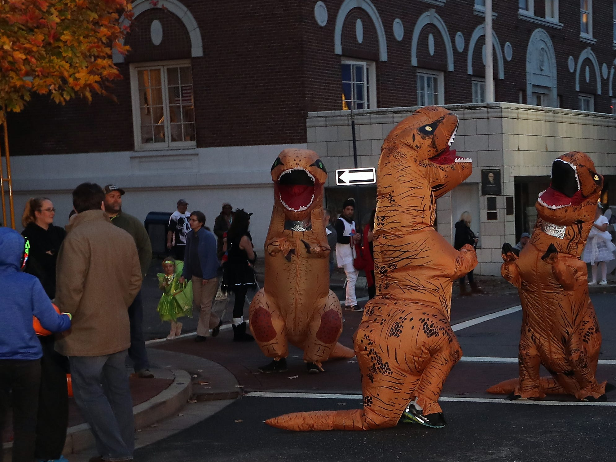 A trio of T-Rex's mingle at the corner of Pacific and 5th during Downtown Bremerton's Trick or Treat Street on Wednesday, October 31, 2018.