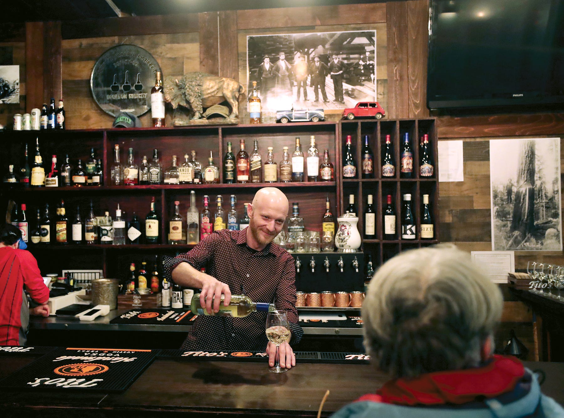 Tanner Baughman has launched a couple new endeavors on the island: Timber, a new steakhouse/bar, in the Bainbridge Pavilion, alongside a new Uber Eats imitator called IslandBite. Drivers deliver from Timber and a handful of other Bainbridge restaurants straight to your door.He is filling a drink for a customer at the bar on Wednesday, October 31, 2018. The restaurant / bar has a wood theme inside.