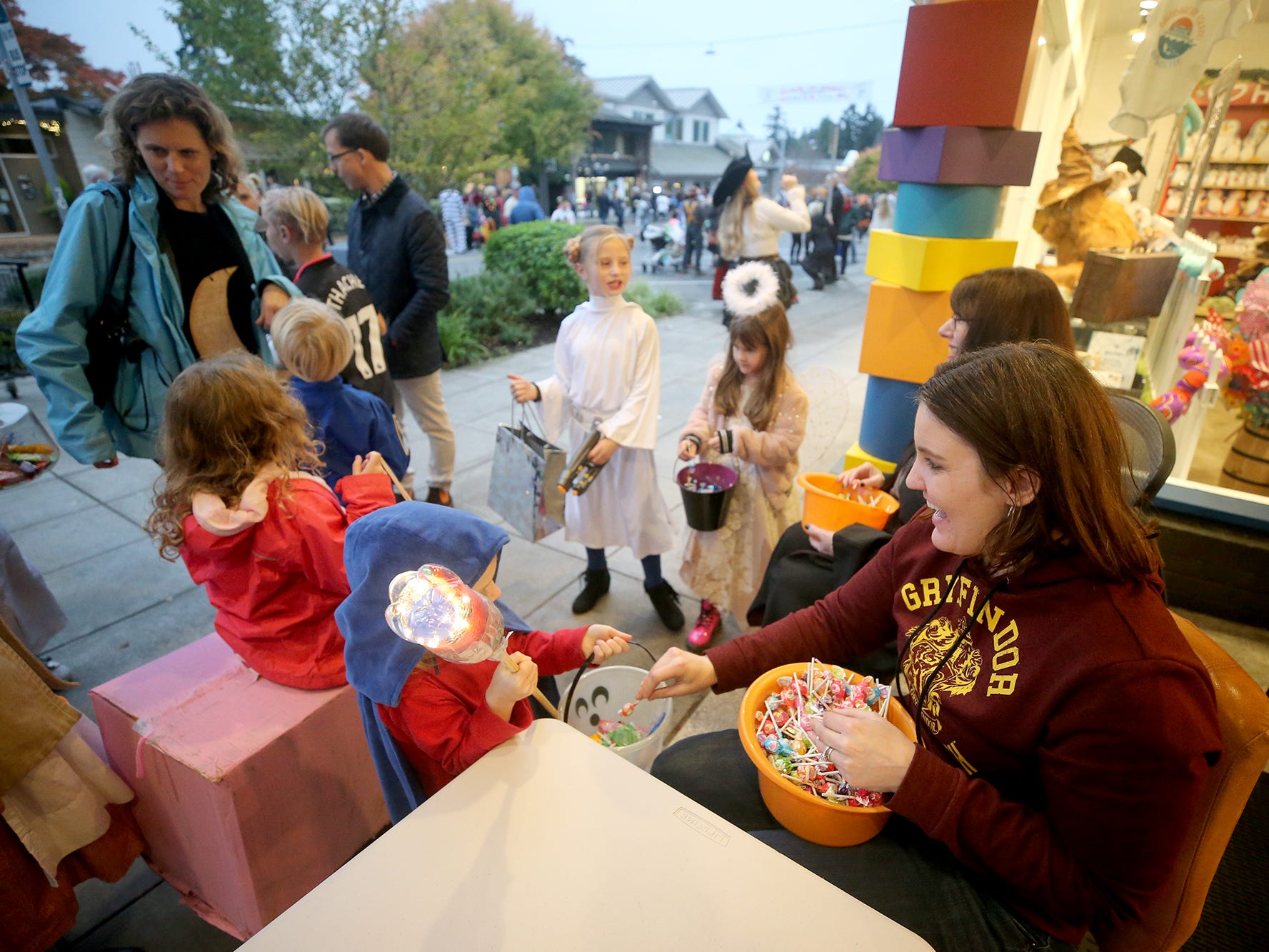 Lauren Trujillo, right, hands out candy in front of the Calico Toy Shoppe at the Bainbridge Island Halloween Walk on October, 31, 2018.