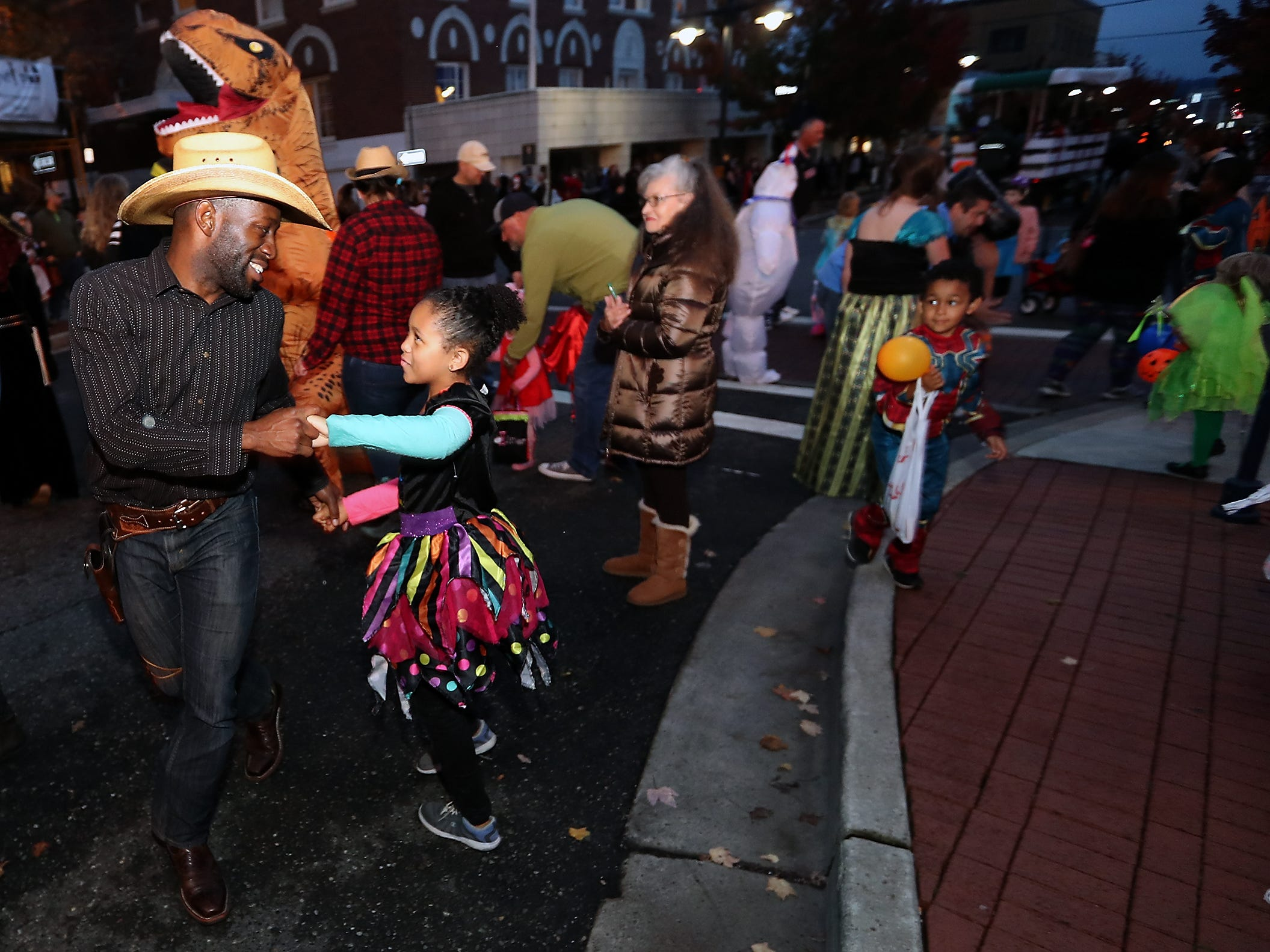 Fidel Forde dances with his daughter Adeline, 9, to the music filling the street in front of the Admiral Theatre during Downtown Bremerton's Trick or Treat Street on Wednesday, October 31, 2018.