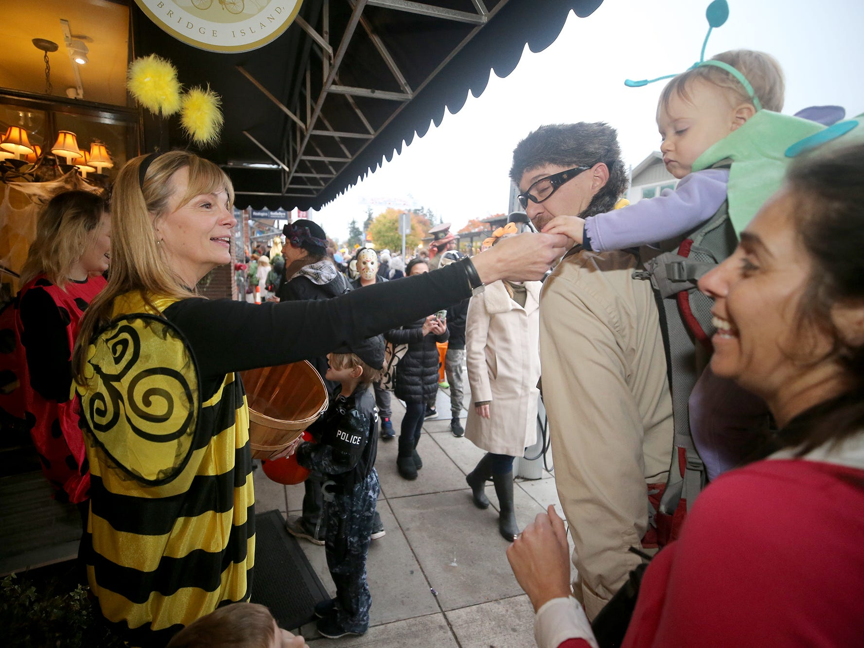 Lisa Wangen hands out candy while dressed as a bee for the Bainbridge Island Halloween Walk on October, 31, 2018.