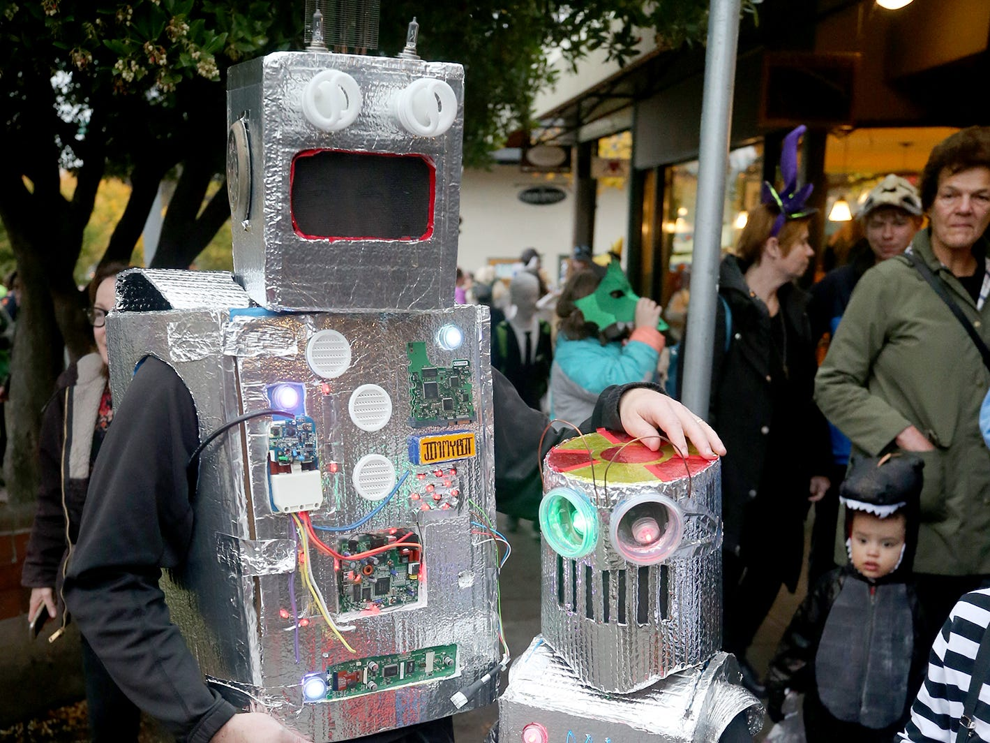 Jim Voss, left, and son Regan, 5, of Bainbridge, dressed as father and son robots for the Bainbridge Island Halloween Walk on October, 31, 2018.