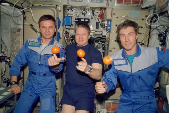 On Dec. 4, 2000, the Expedition One crew members are about to eat fresh oranges onboard the Zvezda Service Module of the Earth-orbiting International Space Station. Pictured, from the left, are cosmonaut Yuri Gidzenko, Soyuz commander; NASA astronaut William Shepherd, mission commander; and cosmonaut Sergei Krikalev, flight engineer.