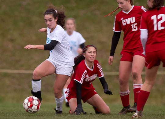 South Burlington's Josie Oliveira, left, plays out of pressure from Champlain Valley's Jess Klein, center, and Olivia Morton during Wednesday's Division I girls soccer semifinal in Hinesburg.