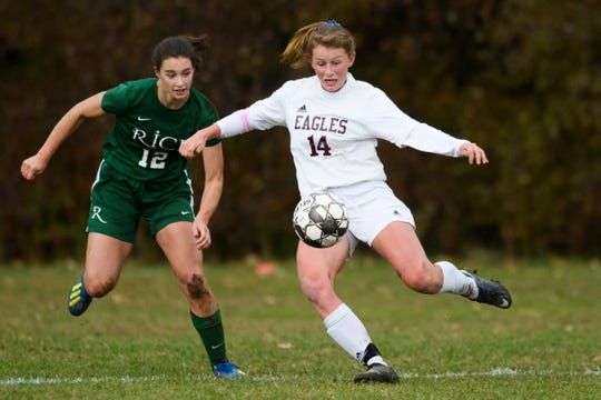 Mt. Abe's Addy Harris (14) kicks the ball past Rice's Petra Langan (12) during the girls soccer semifinal game between Mount Abraham Eagles and the Rice Green knights at Rice Memorial High School on Wednesday afternoon October 31, 2018 in South Burlington.