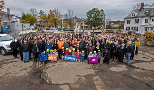 Community members pose for a group photo after a ceremony to celebrate the construction of the Burlington YMCA's new home on College Street in Burlington on Thursday, November 1, 2018.