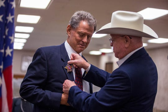 Neuces County Sheriff Chris Hooper (left) receives his badge from outgoing Sheriff Jim Kaelin during the ceremony in which Hooper officially became sheriff at the Nueces County Courthouse on Thursday, November 1, 2018.