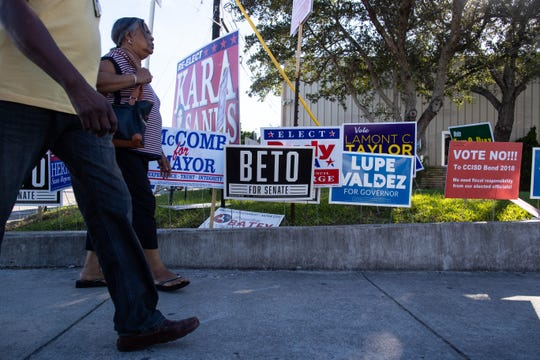 Voters walk past a political signs in front of the Deaf & Hard of Hearing Center an early voting location on Thursday, Nov. 1, 2018.