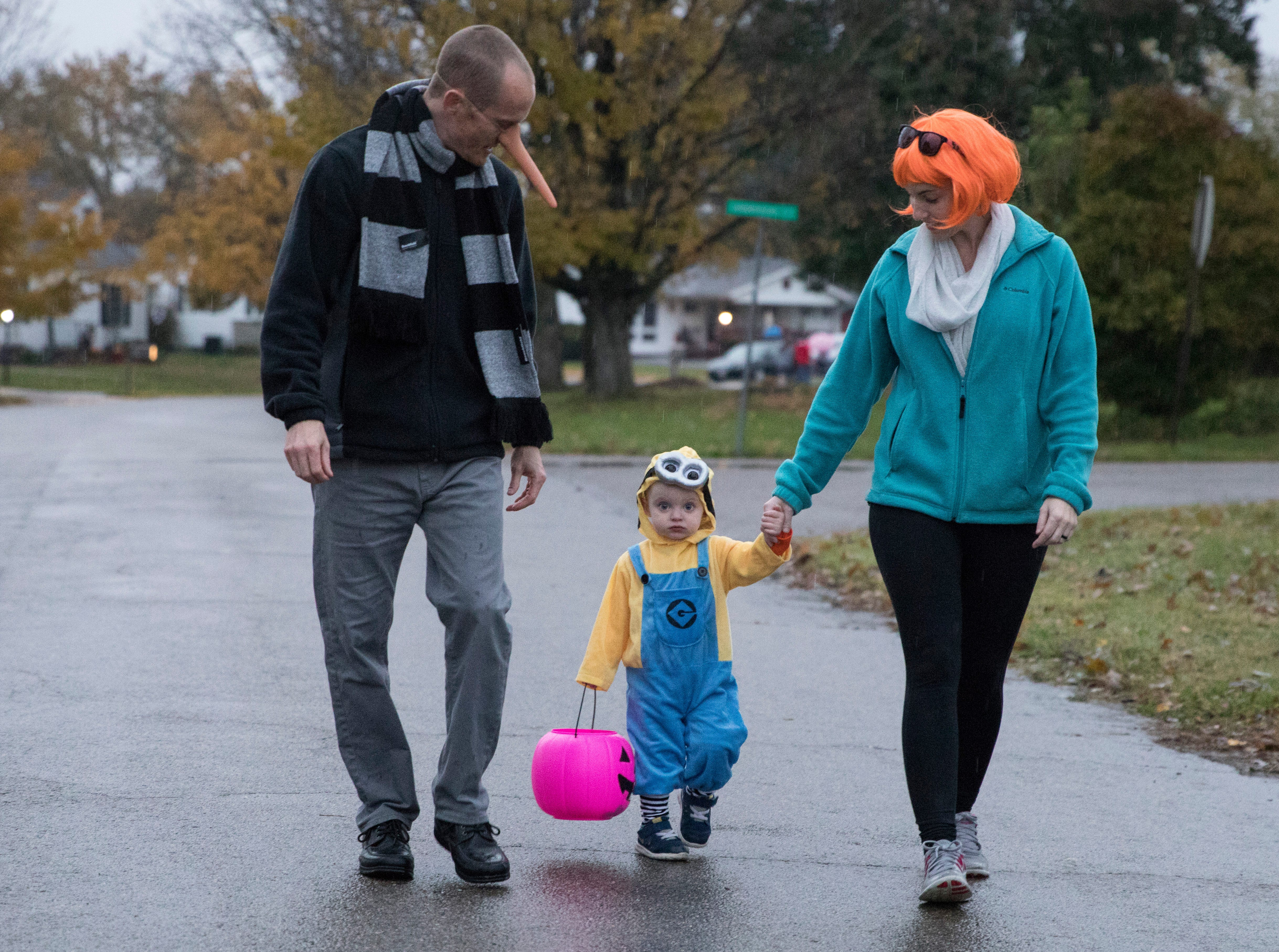 Madelyn Grahm, 2, trick-or-treats with her parents near the Save-A-Lot in Chillicothe Wednesday evening.  The rain and mud did not stop residents from collecting candy on trick-or-treat night on October 31, 2018.