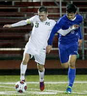 McNicholas forward Grant Murray tries to fend off Bexley defender Grant Halliday during their Division II boys regional soccer tournament game at London Wednesday, Oct. 31, 2018.