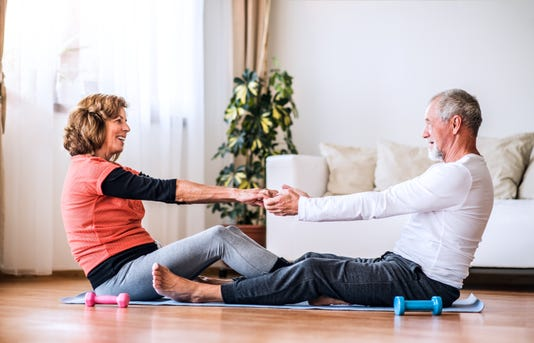Senior Couple Doing Exercise At Home