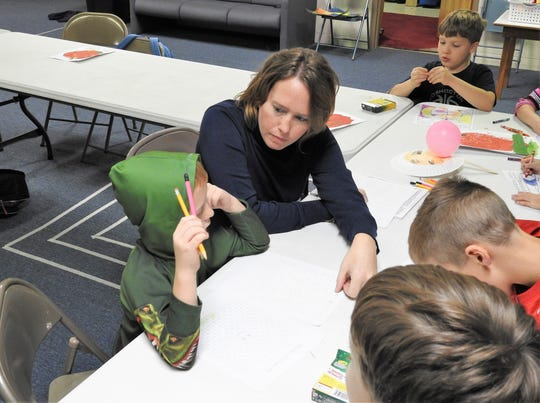 Jennifer Graham works with students on an art project in STEAM Class at the Coshocton Christian Learning Co-Op. Lessons for kindergarten to third grade students focuses on science, technology, engineering, arts and math.