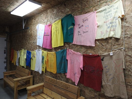 T-Shirts part of the Clothesline Project hang in the new office building for First Step Family Violence Intervention Services. The shirts illustrate the stories of those abused with the color of shirt denoting the type of violence faced.