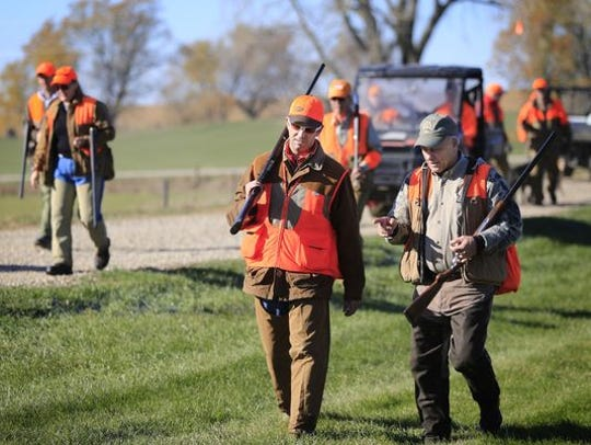 Donald Trump Jr. and Rep. Steve King talk after hunting pheasants at the Hole 'N The Wall Lodge near Akron, Iowa Saturday, Oct. 28, 2017. Trump Jr. is wearing sunglasses and is toting a shotgun on shoulder while talking with King.