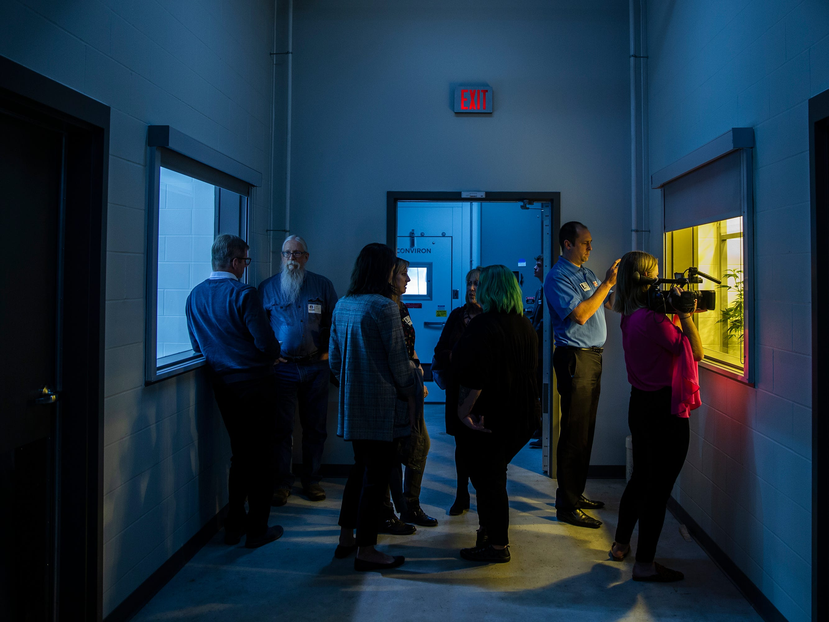People crowd around the windows giving a view inside the cannabis growing rooms inside MedPharm's medical-marijuana production facility during an open house on Thursday, Nov. 1, 2018, in Des Moines.