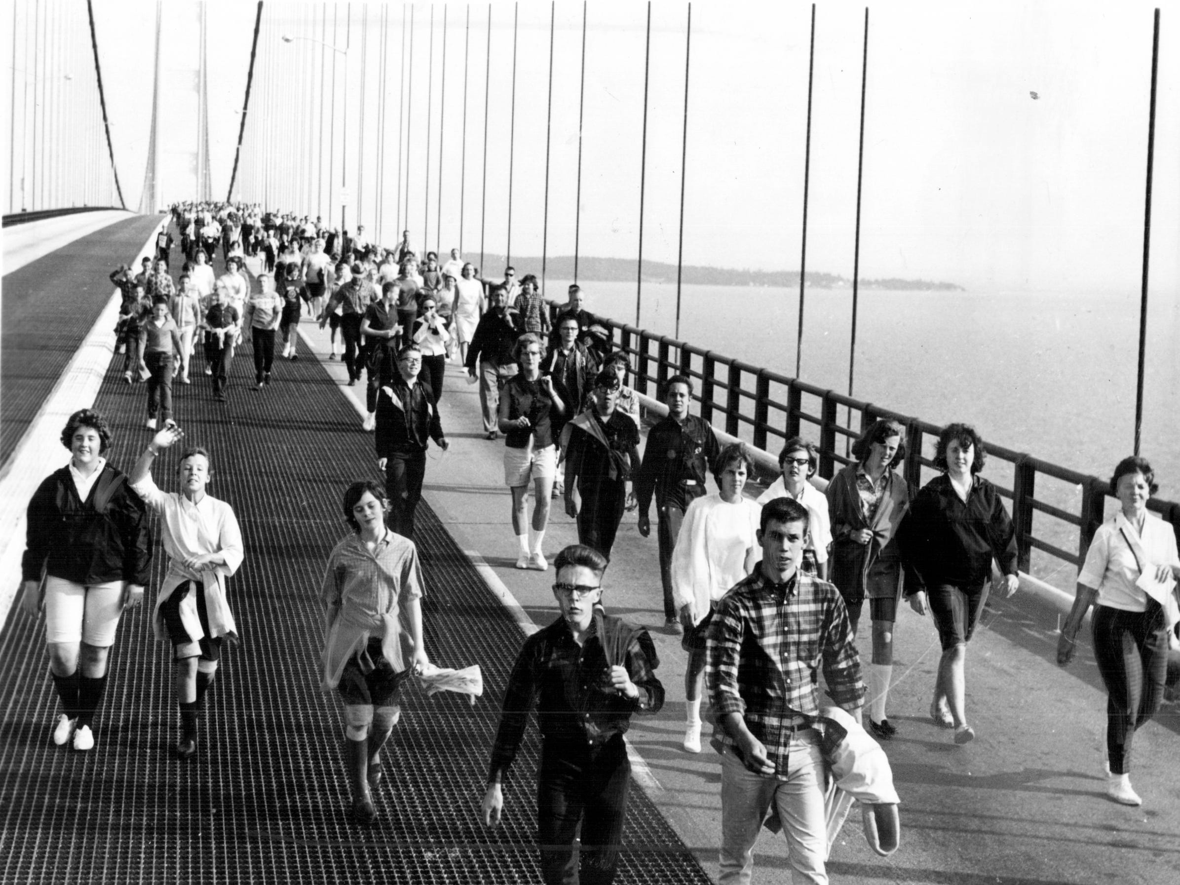 Normally, pedestrians are not allowed on the Mackinac Bridge, the 4 ½ - mile kink between Michigan's Upper and Lower Peninsulas. But it's a different story each Labor Day when the bridge is opened to hikers. More than 10,000 are expected to walk across Mighty Mac, from St. Ignace to Mackinaw City, beginning at 8:30 a.m. Labor Day. Shown here are a few of the 9000 persons who took part in 1964. Certificates are given to all who complete the walk.