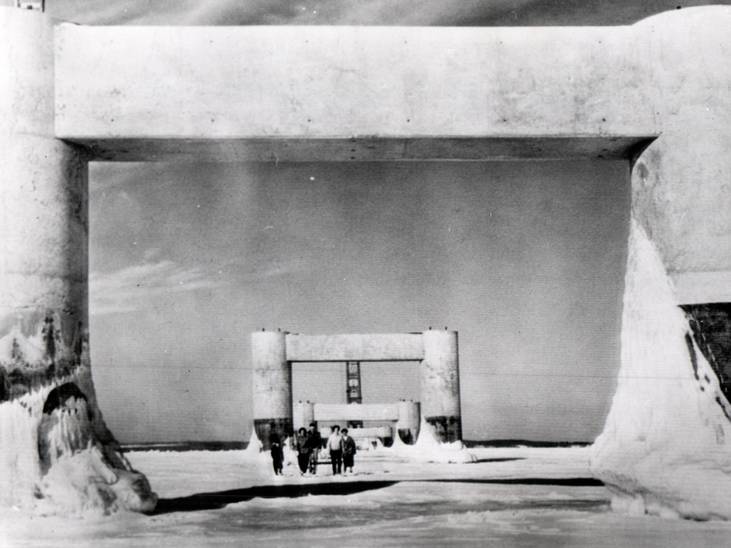 Mackinaw City - Feb. 15, 1956. Photo shows one of the big arches of the bridge, its bases sheathed in ice, forms a frame for the five Mackinaw City residents who are returning to shore from a close-up inspection of the span.