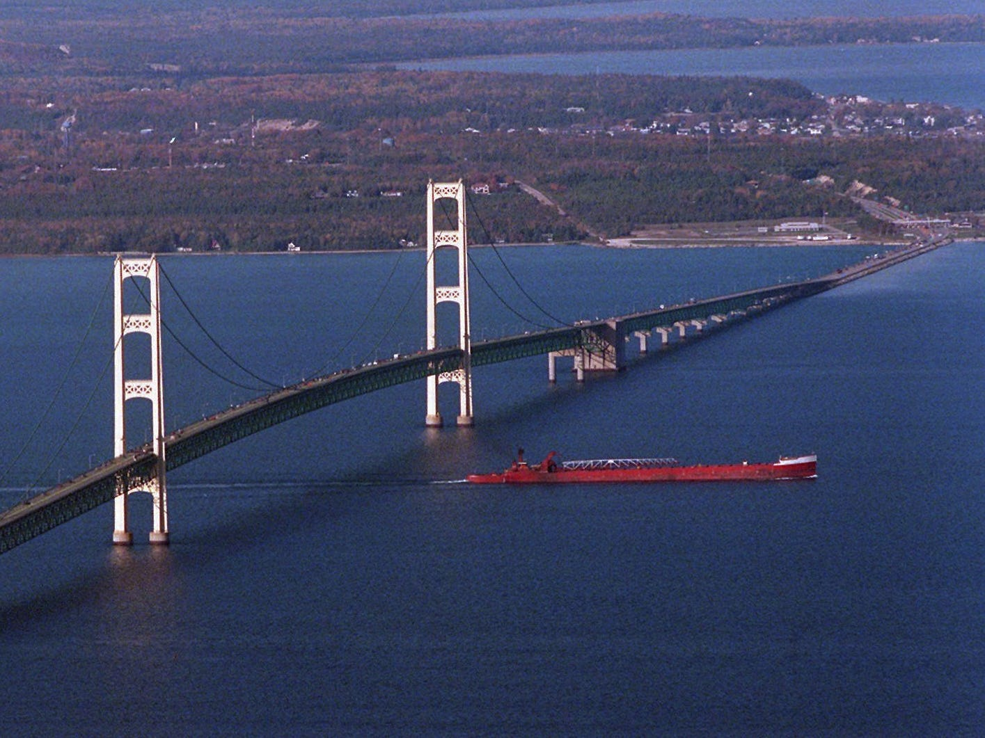 A barge makes its way past the Mackinac Bridge, in this Oct. 1997 file photo. The bridge which  is a  5-mile steel and concrete structure that opened 40 years ago this Saturday, Nov 1, 1997, is a testament to the hard work of thousands of  workers. It is the only bridge connecting the Upper Peninsula to the rest of Michigan.