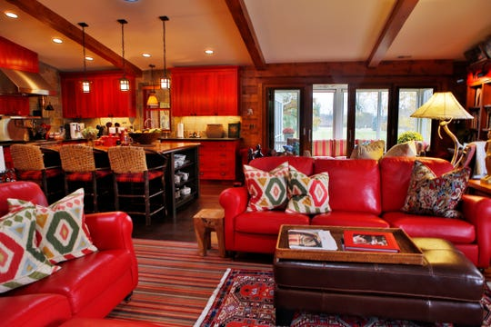 Leather sofas in the greatroom echo the brilliant red of the custom cabinets.