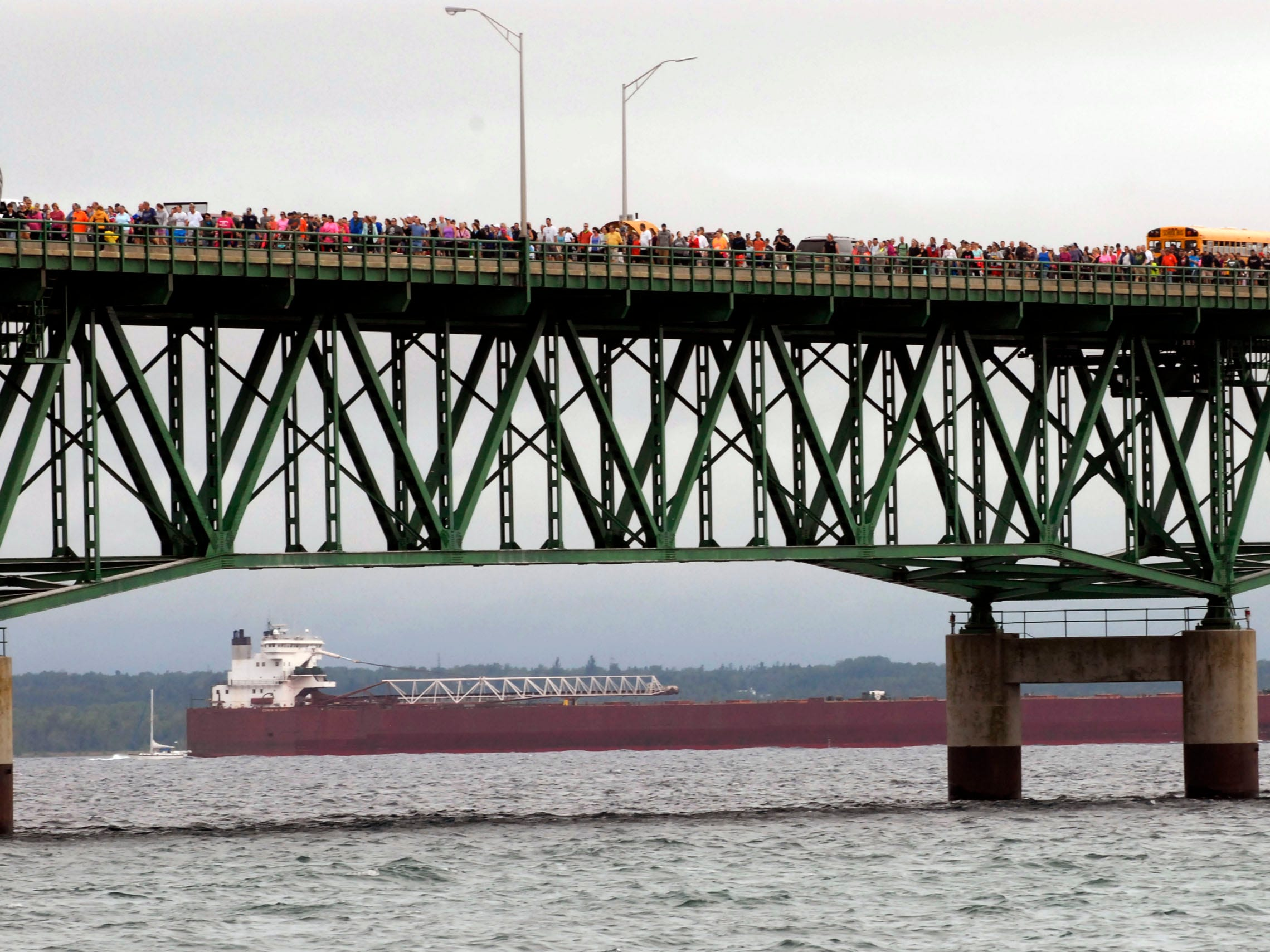 Pedestrians walk the Mackinac Bridge, Monday, Sept. 7, 2015, as an ore freighter approaches to pass under the span, in Mackinaw City, Mich. Labor Day is the only day walkers are allowed on the span, which connects Michigan's upper and lower peninsulas.