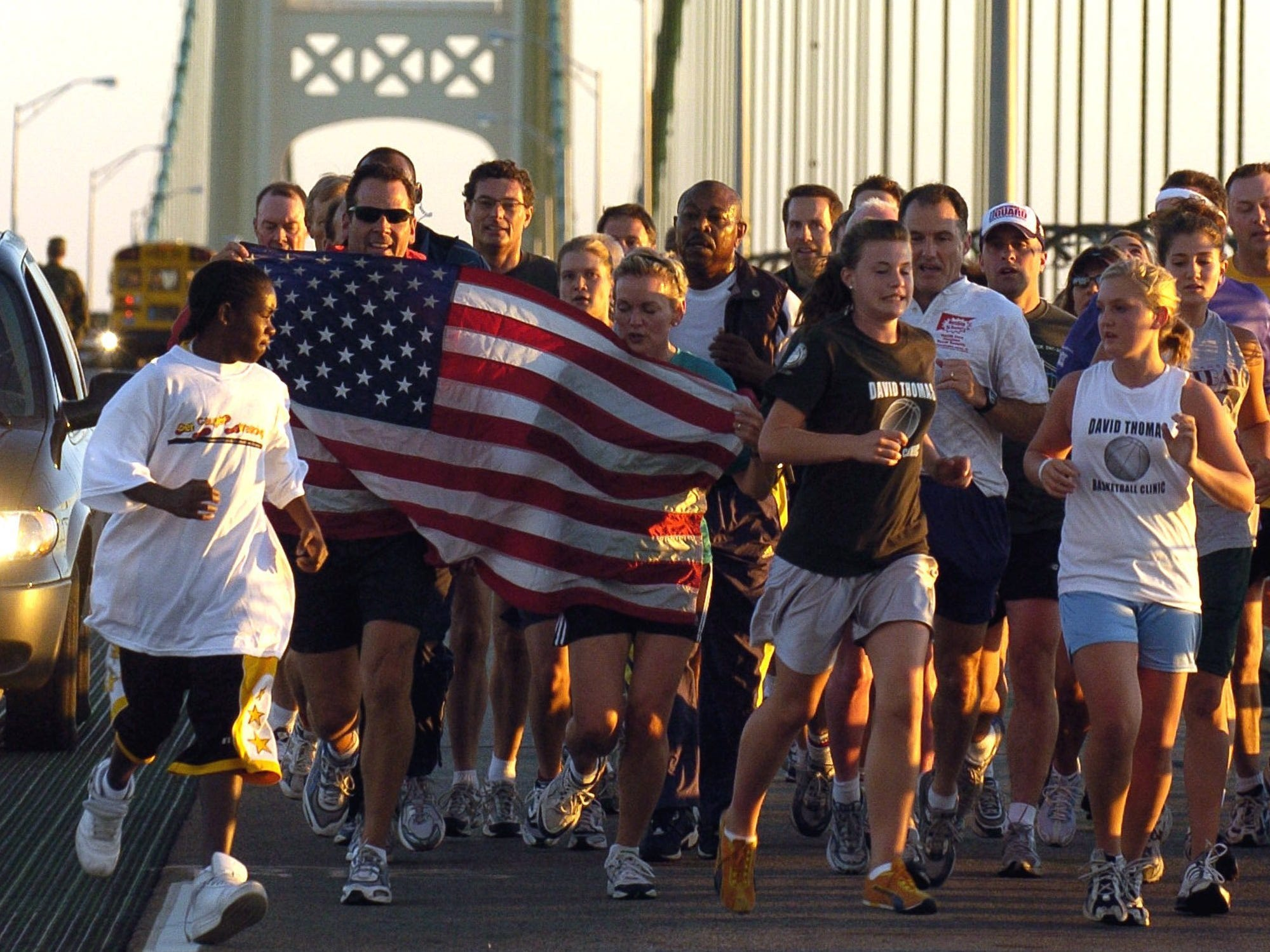 Michigan Gov. Jennifer Granholm, behind stripes on American flag, center, joins thousands of people walking and running across the five-mile Mackinac Bridge, Monday, Sept. 5, 2005, near Mackinaw City. By custom, the governor leads the walk.