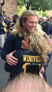 Michigan defensive end Chase Winovich hugs his mother, Anina, before one of his college football games.