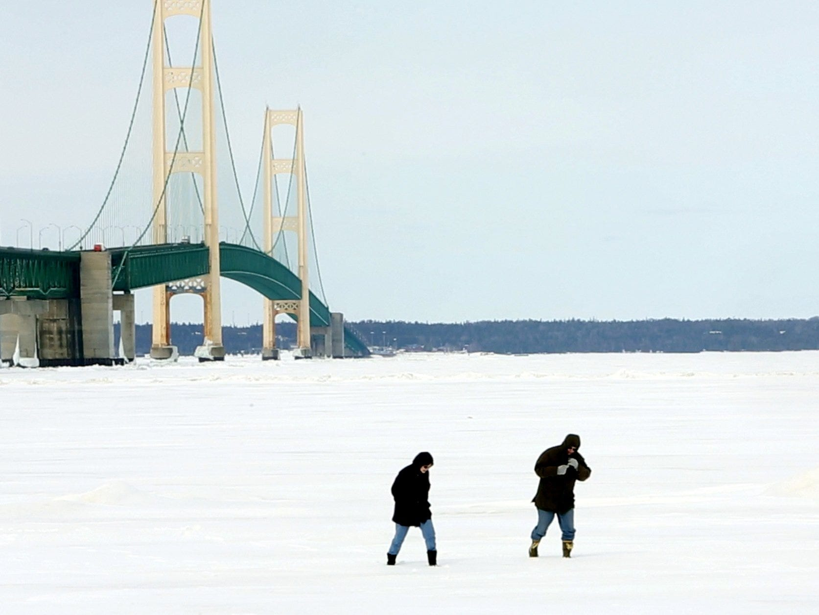 People walk on the frozen waters of the Straits of Mackinac near the Mackinac Bridge as seen from Mackinaw City on Friday, March 21, 2014.