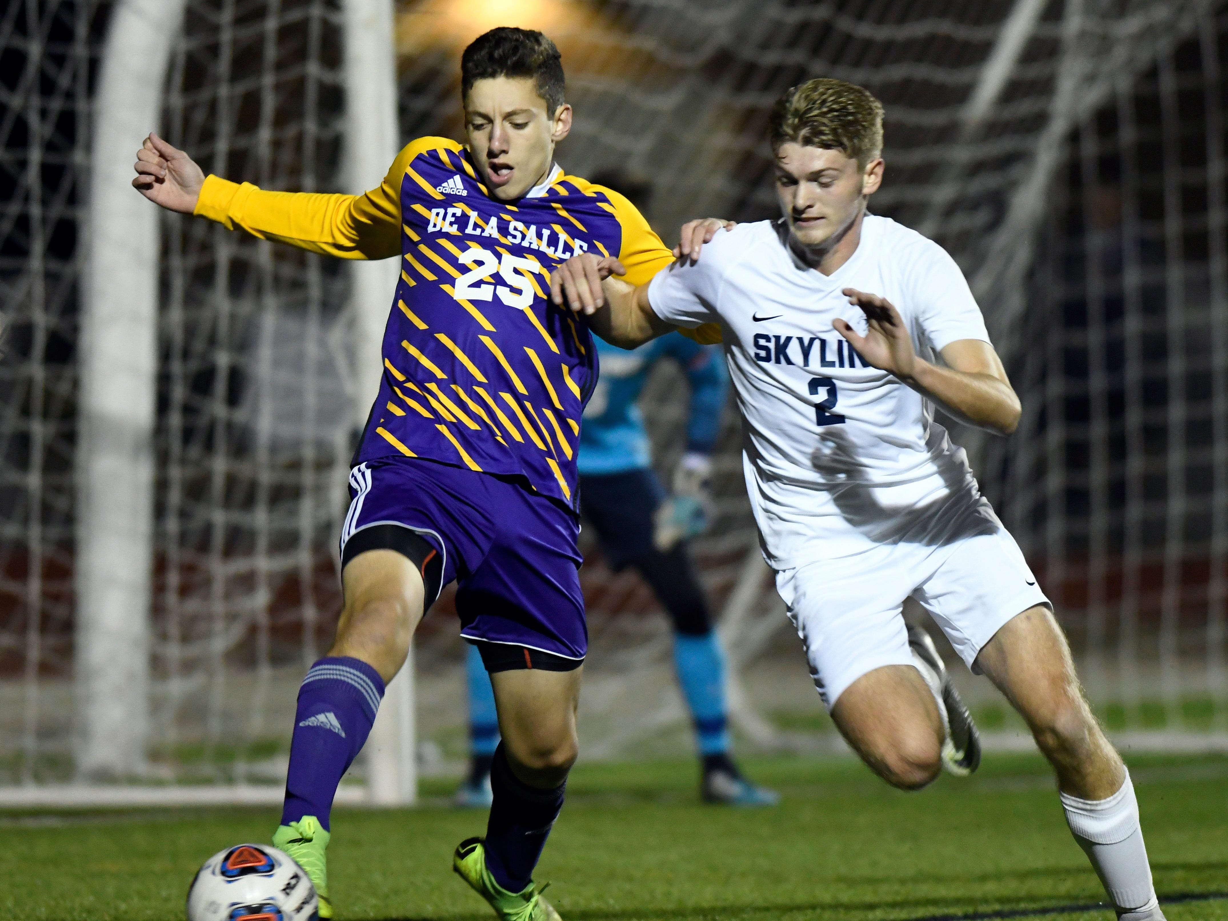Fighting for the ball are Warren De La Salle midfielder Spencer LeBeau (25) and Ann Arbor Skyline player Jamie Palms (2) during the first half.