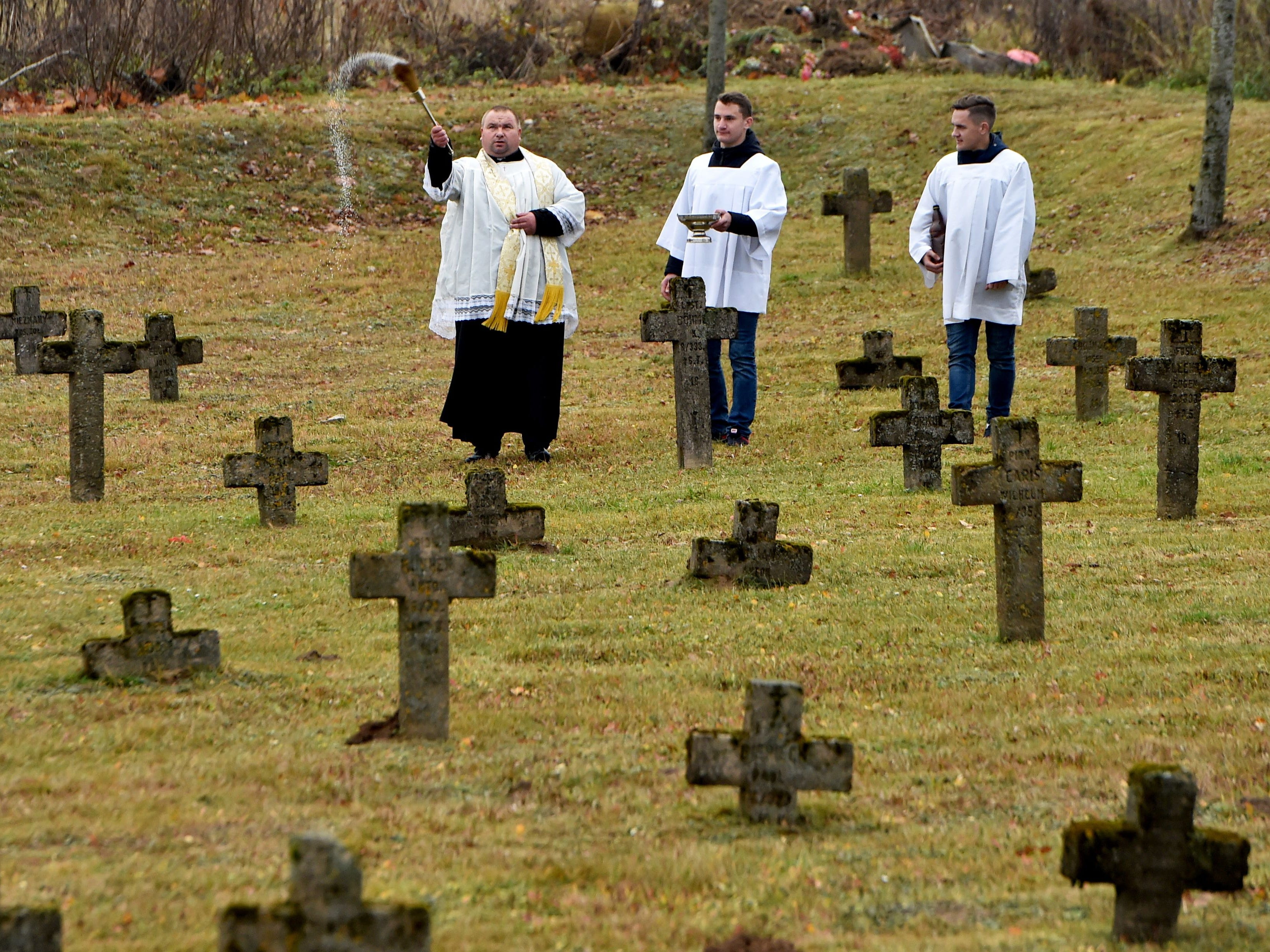 This Belarus' Catholic priest blesses graves at a cemetery during the All Saints' Day in the village of Baruny on November 1, 2018.