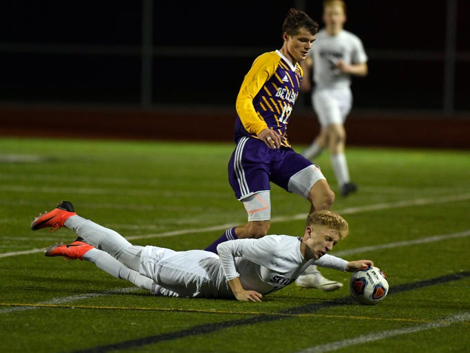 Ann Arbor Skyline defenseman Austin Sarns-Moy (18), bottom, is knocked down as he is fouled by Warren De La Salle defenseman Tadeusz Gabryel (17), who was given a yellow card for this play, during the first overtime.