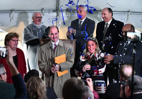 Trenton Mayor Kyle Stack, Matthew Moroun of Crown Enterprises, U.S. Congresswoman for the 12th District Debbie Dingell and other dignitaries launch party poppers after the deed transfer.  Ceremony to celebrate the transfer of the former McLouth Steel Plant parcel from the Wayne County Land Bank to Crown Enterprises outside the plant in Trenton, Michigan on November 1, 2018.