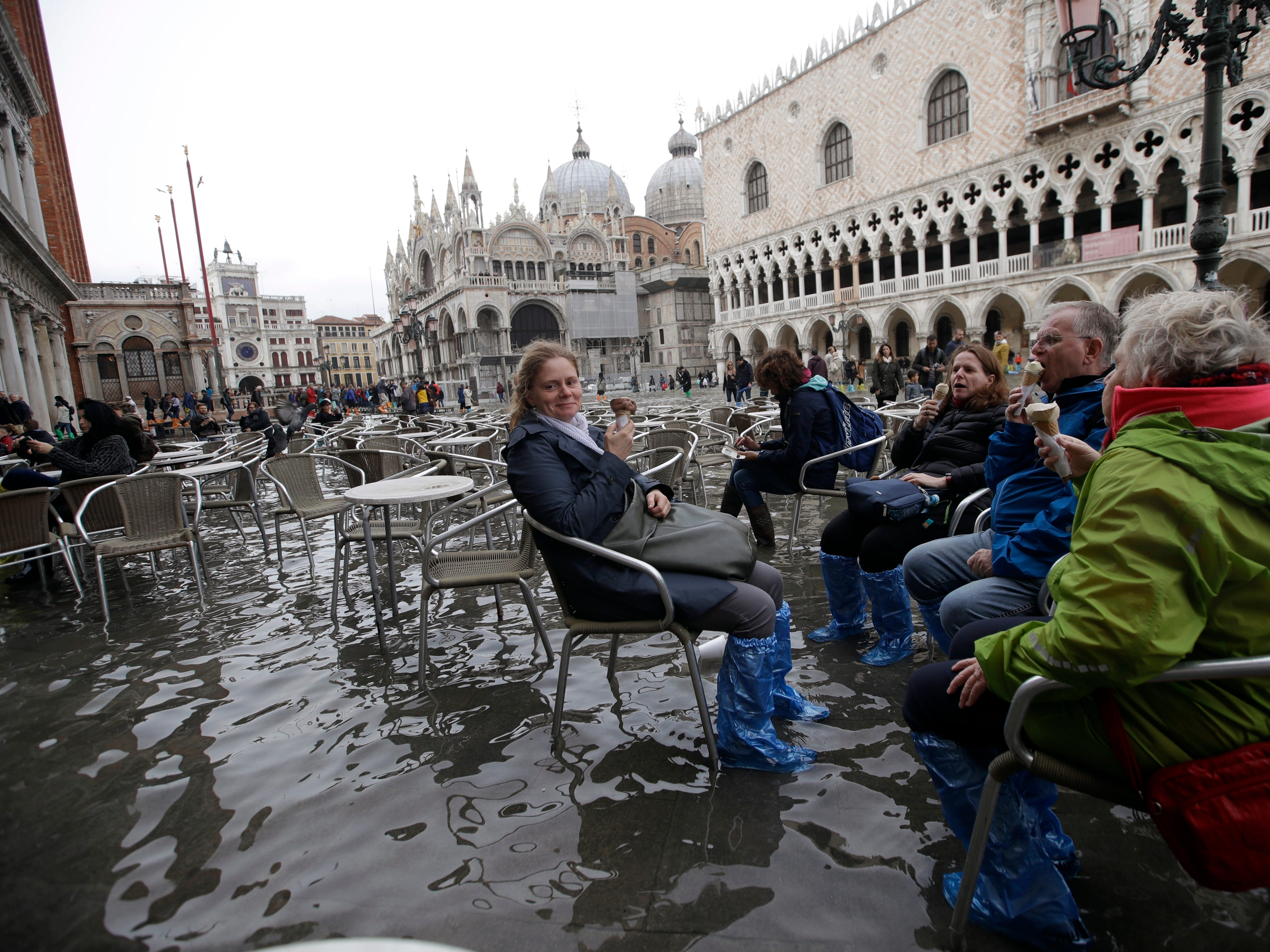 Tourists enjoy an ice cream as they sit in the flooded St. Mark's Square in Venice, Italy, Thursday, Nov. 1, 2018, as rainstorms and strong winds have been battering the country. Two people were killed when a falling tree crushed their car in the mountainous countryside in northwestern Italy, as rainstorms and strong winds continued to pummel much of the country.